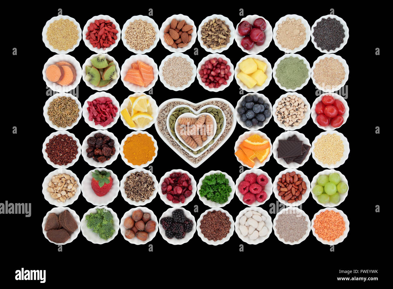Large healthy super food collection in porcelain crinkle bowls over black background. High in vitamins and antioxidants. - Stock Image
