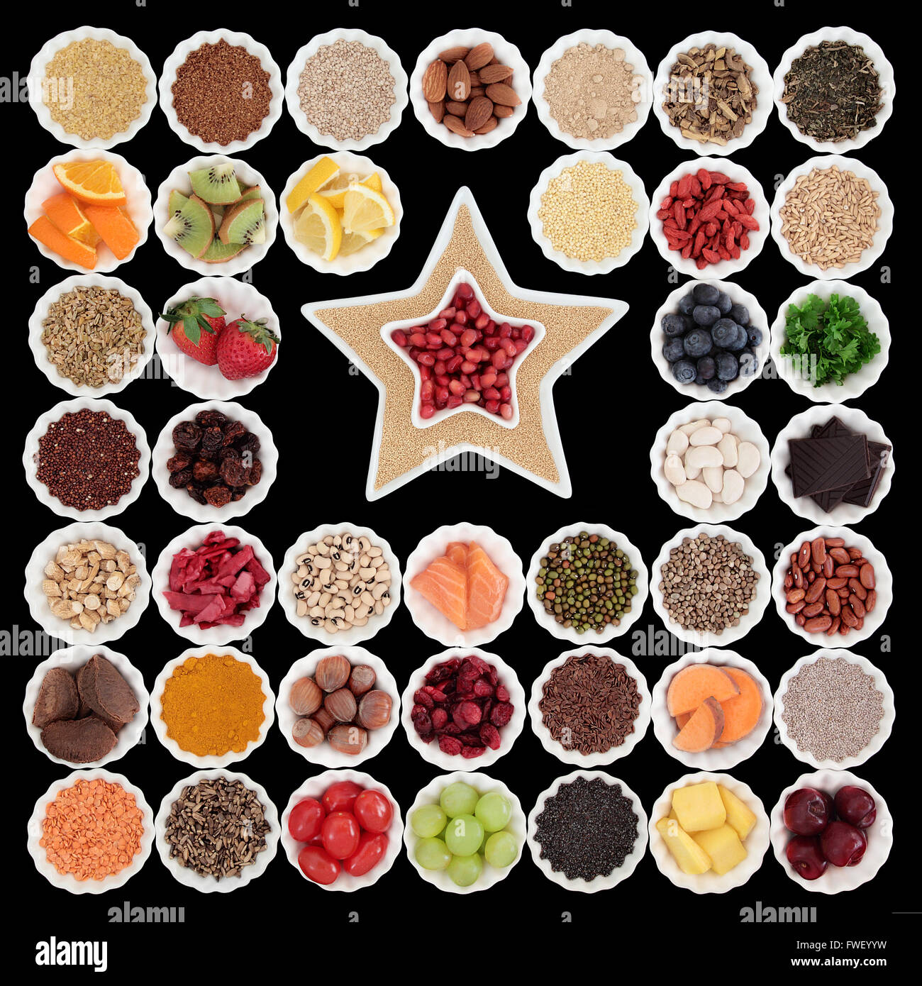 Large health and super food collection in porcelain bowls with star shaped dishes over black background. - Stock Image