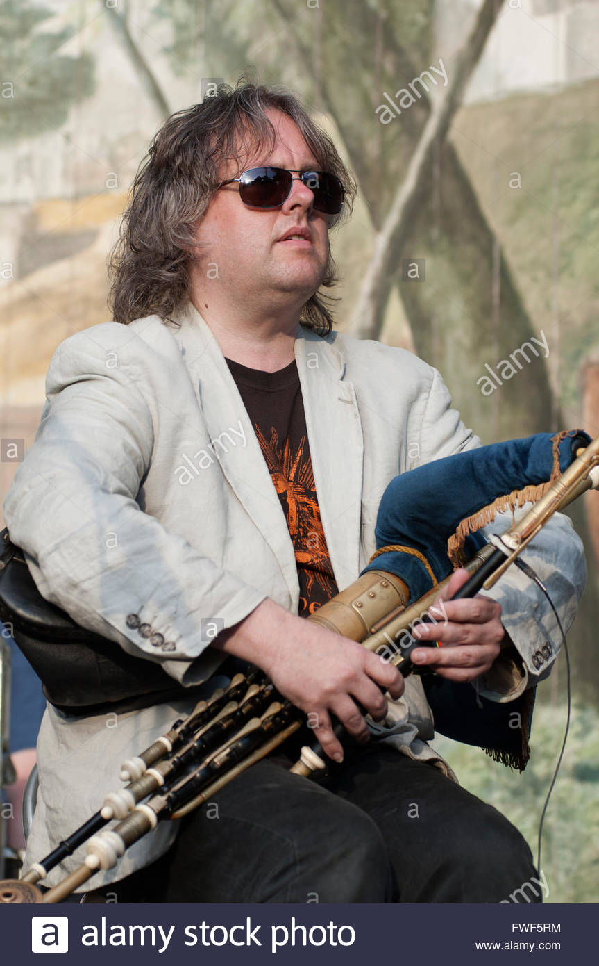 Troy Donockly playing the Uilllean pipes with Ade Edmondson and the Bad Shepherds performing at the Larmer Tree - Stock Image