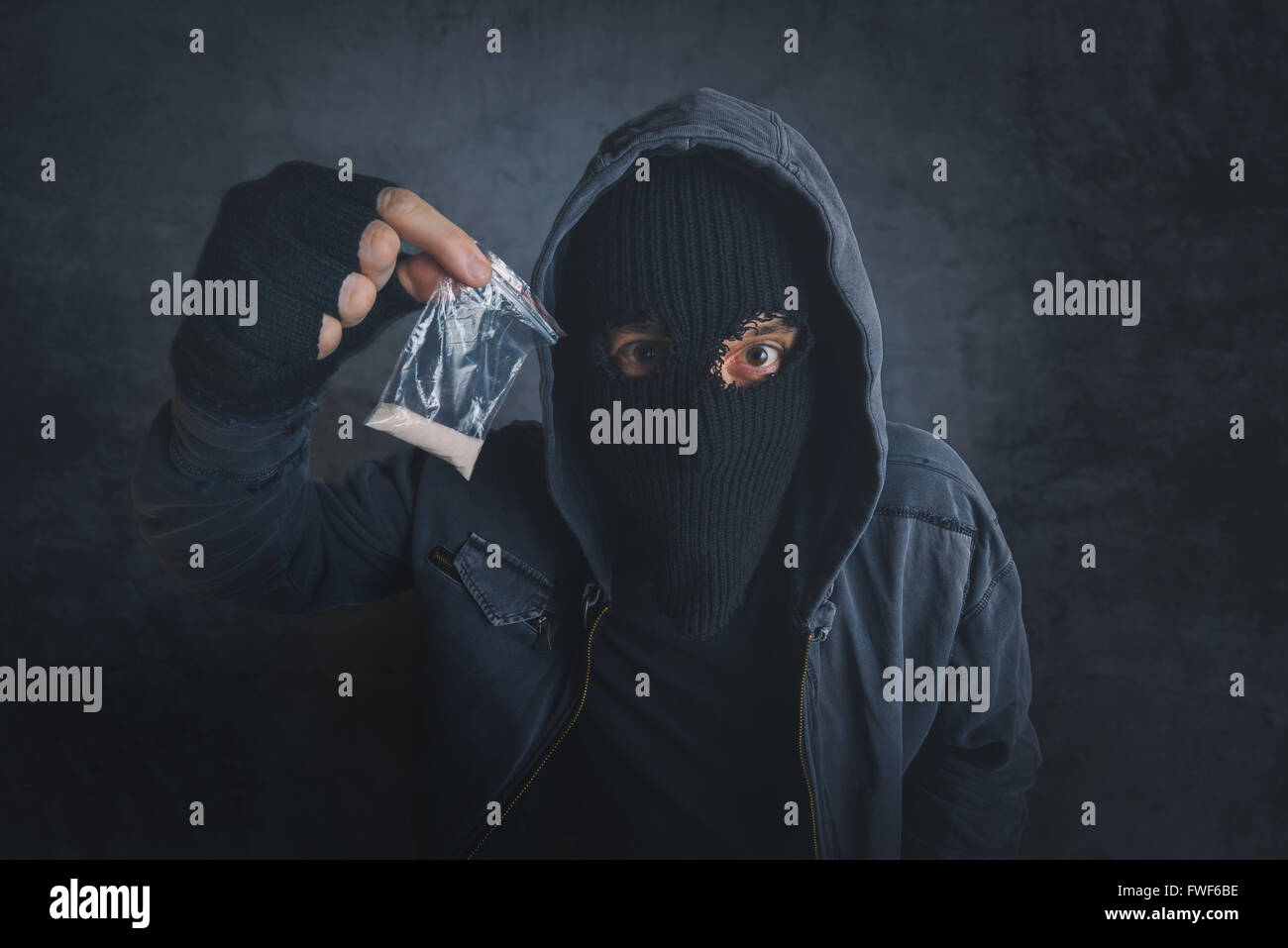 Drug dealer offering narcotic substance to addict on the street, unrecognizable hooded criminal selling drugs in - Stock Image