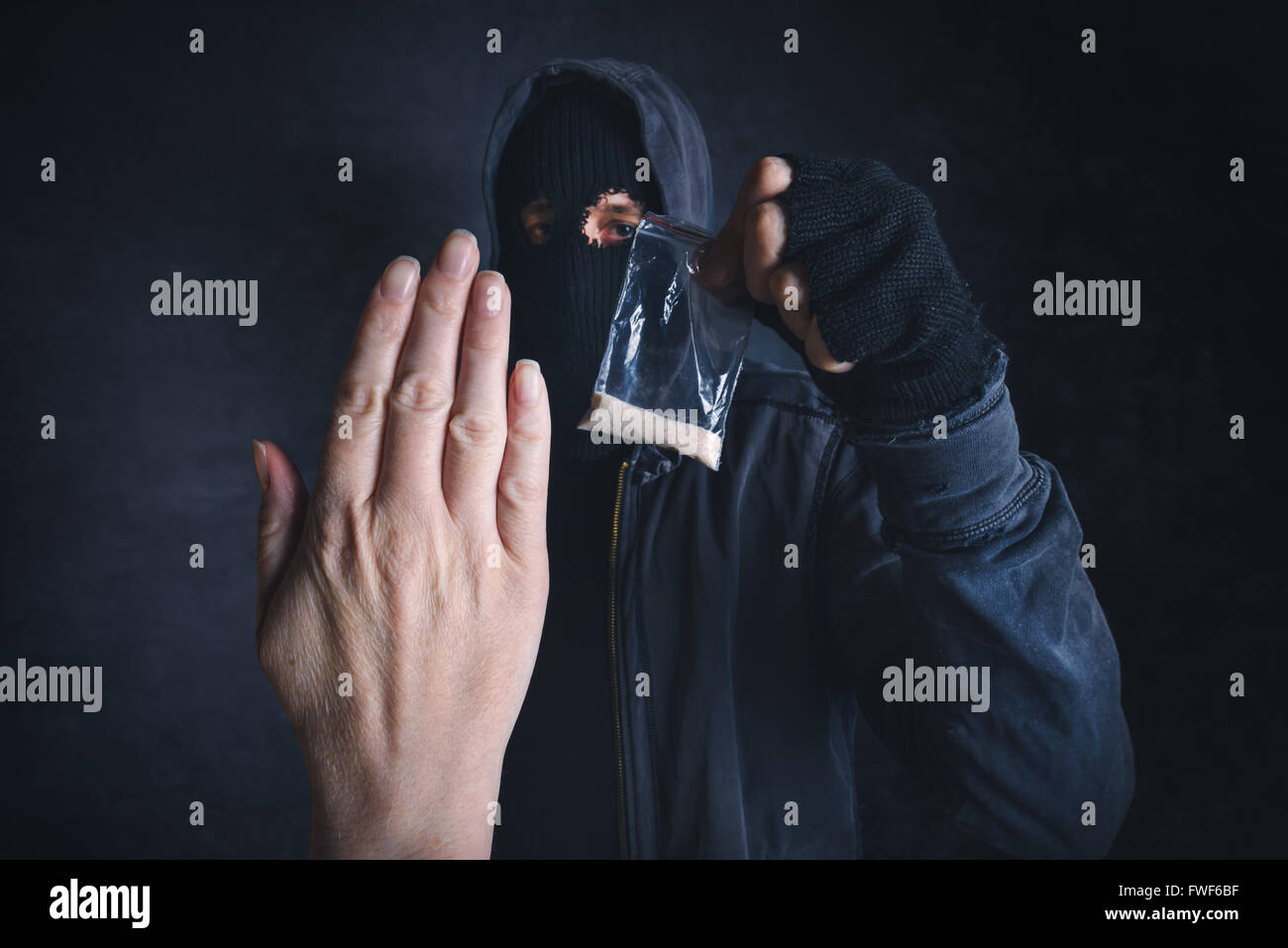 Saying No to drug dealer offering narcotic substance, fight addiction, unrecognizable hooded criminal offering drugs - Stock Image