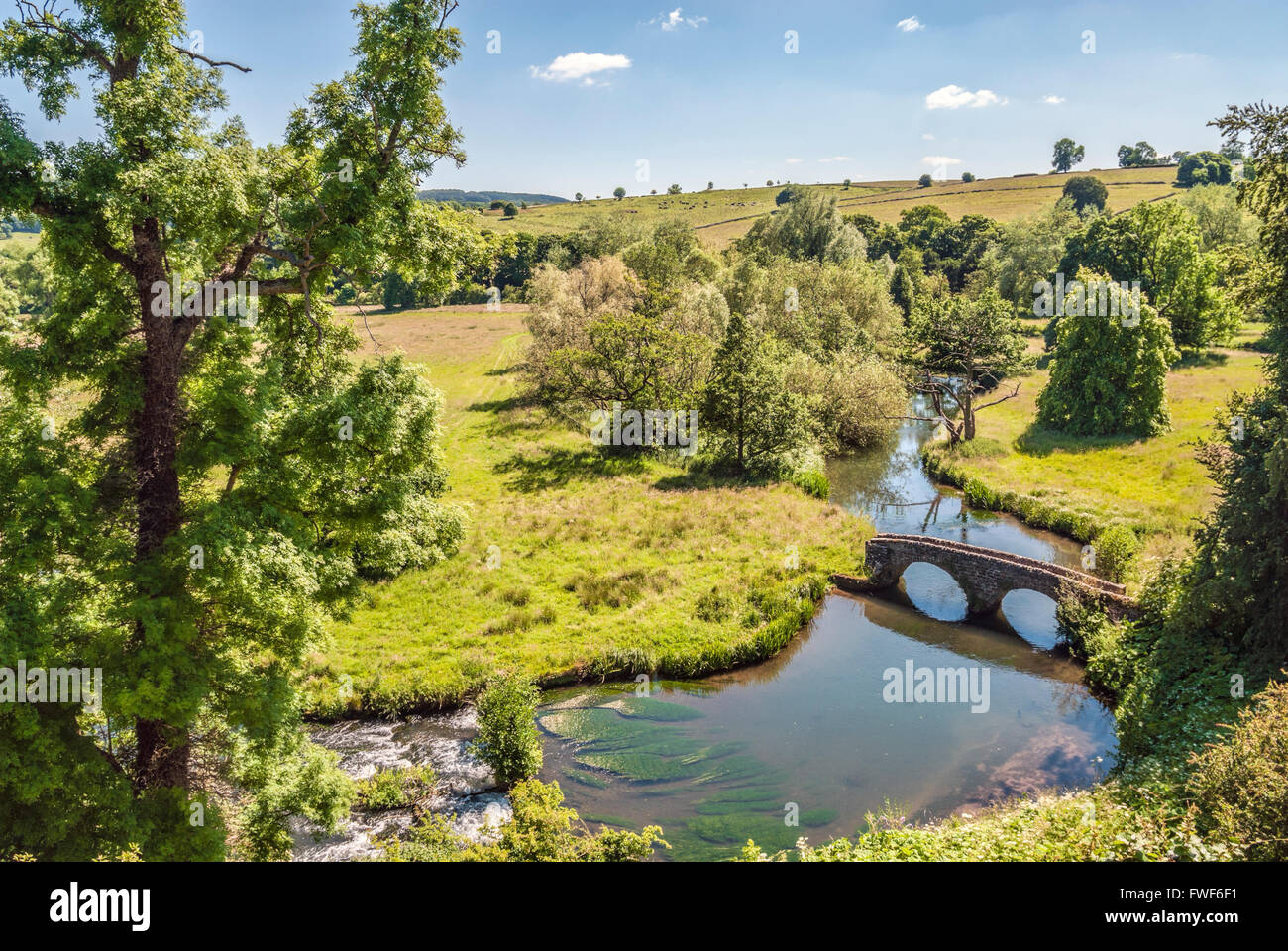 View from the Norman Castle Haddon Hall over the estate and the bridge across the River Wye near Bakewell, Middle - Stock Image