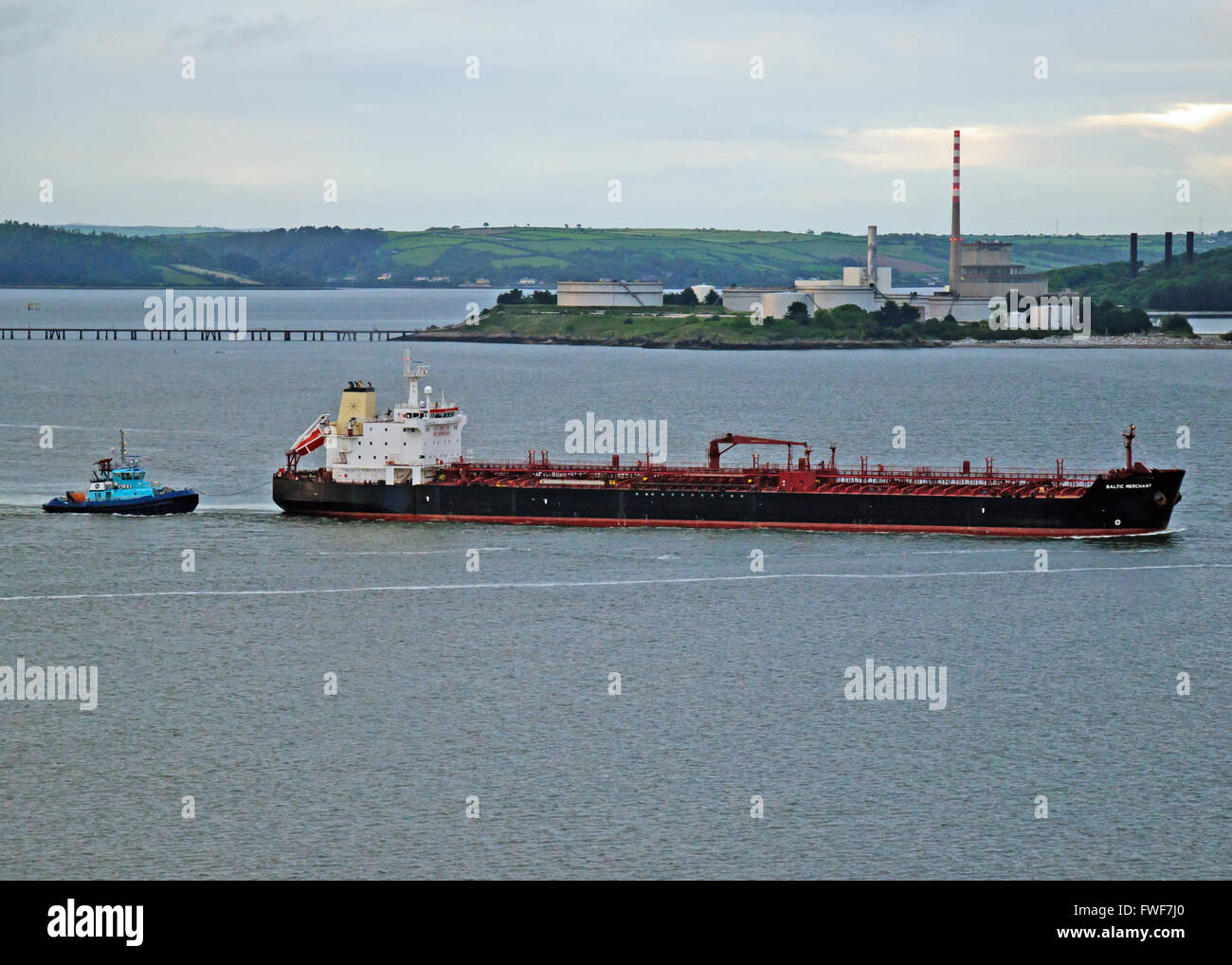 Crude oil tanker Baltic Merchant sails from Whitegate Oil Terminal, Co Cork, Ireland assisted by refinery tug Alex. - Stock Image