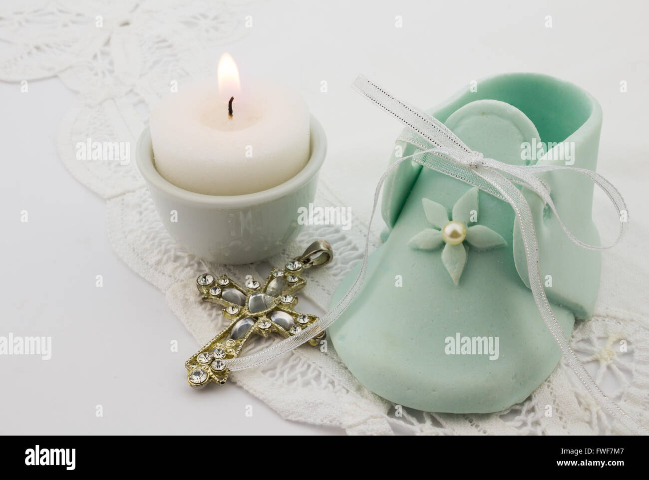 Photo of turquoise fondant baby boot with pearl,crystal cross and lit candle isolated on white lace background - Stock Image