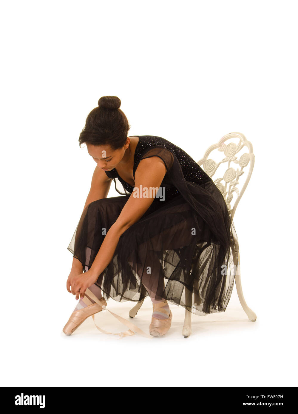 An African American Ballerina ties pointe shoes for dance class - Stock Image