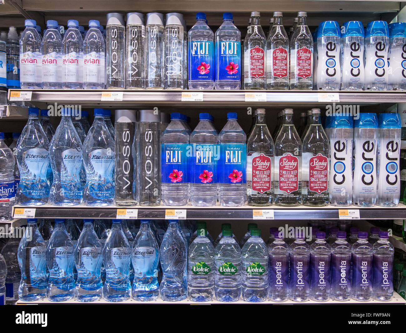 Rows of name brand bottled waters on grocery store shelves. - Stock Image