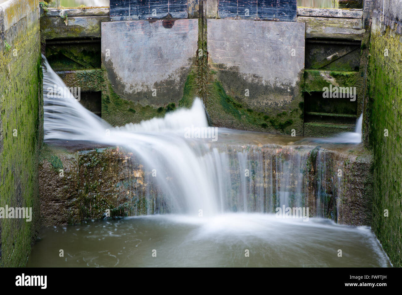 Canal lock cill with water spilling through gate. Lock with water escaping at high pressure through gaps, splashing - Stock Image