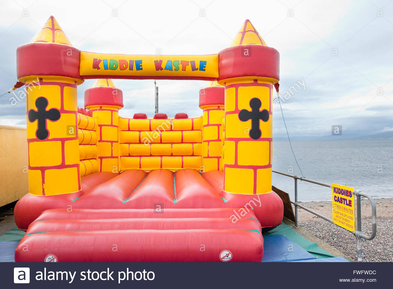 Empty colorful bouncy castle on shore - Stock Image