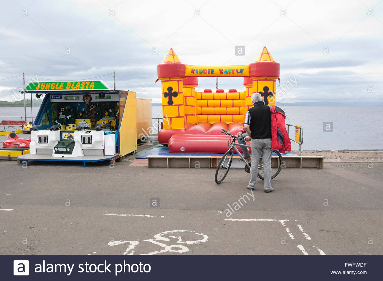 Senior men standing in front of bouncy castle at seaside - Stock Image