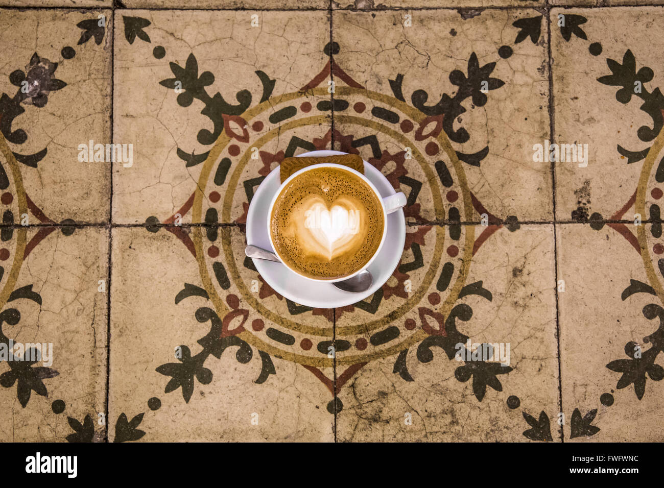 Cafe latte with heart latte art on Spanish tiles - Stock Image
