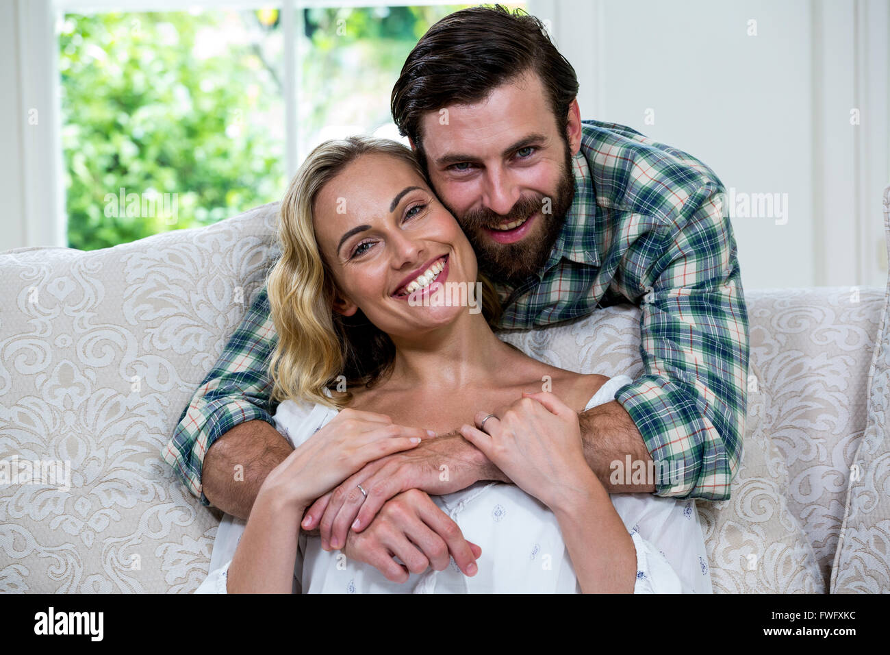 Husband embracing wife from behind against window Stock Photo