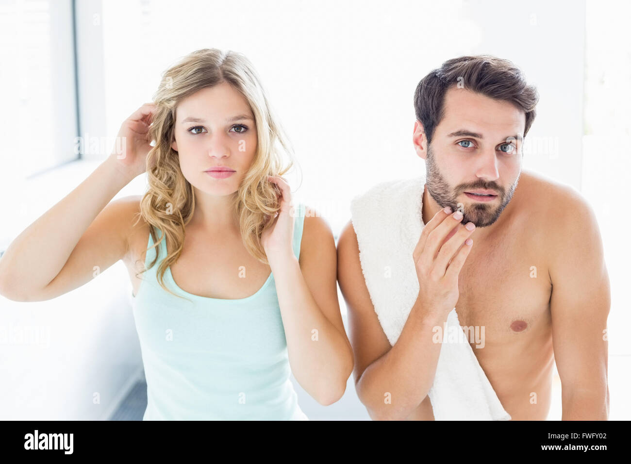 Man and woman checking their skin in bathroom - Stock Image