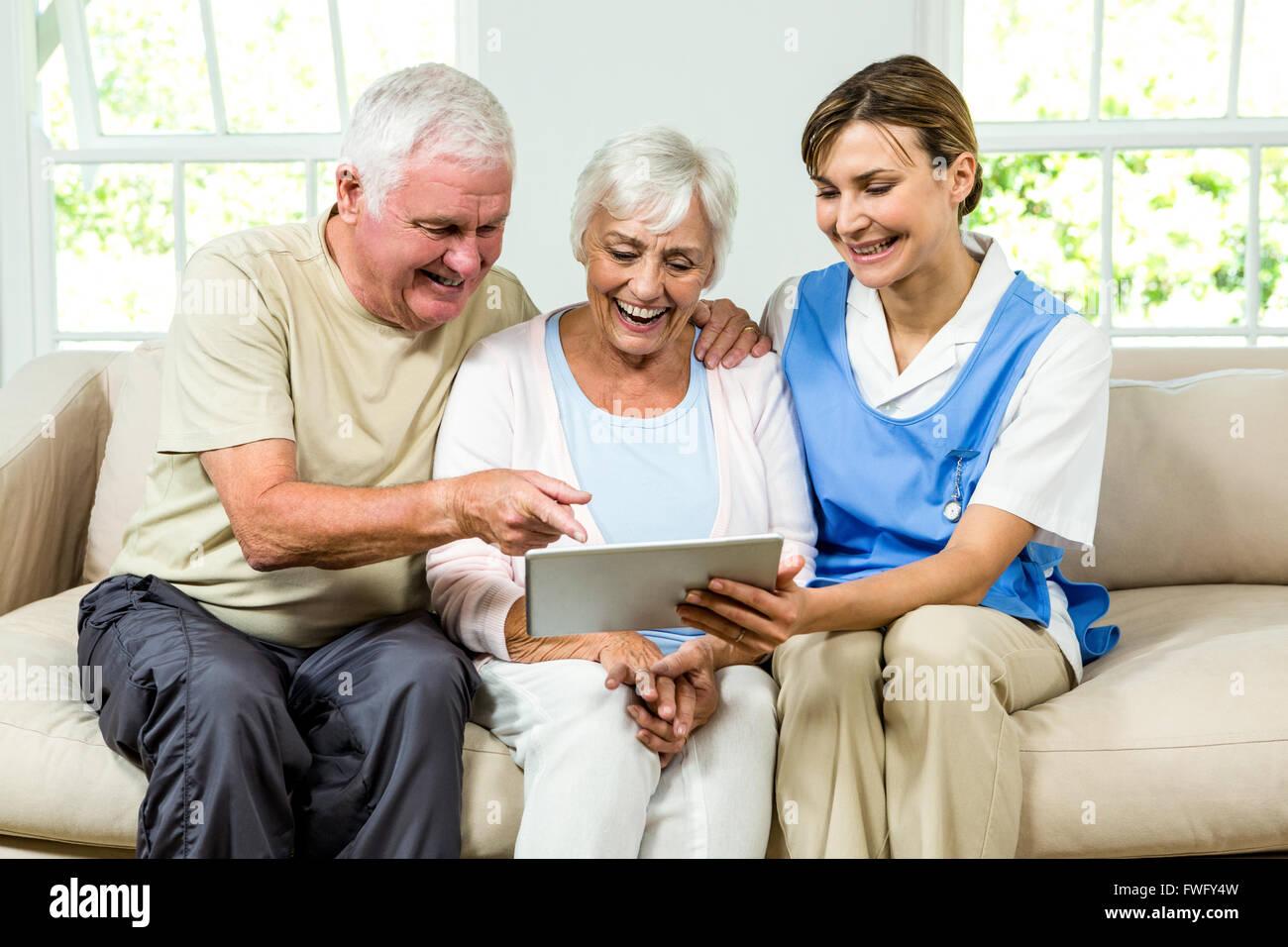 Happy nurse and senior adults holding digital tablet - Stock Image