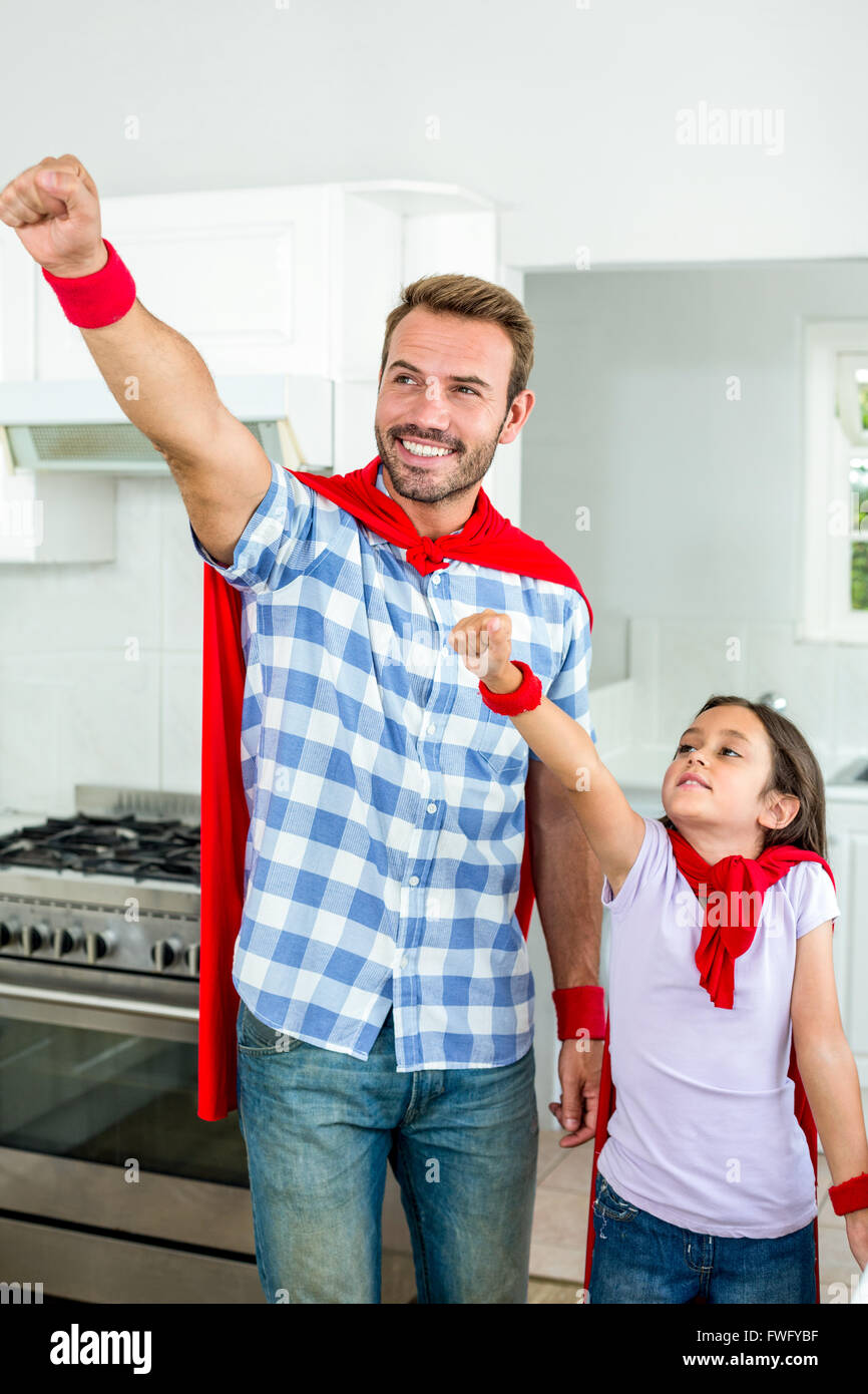Father and daughter in superhero costume with hand raised - Stock Image