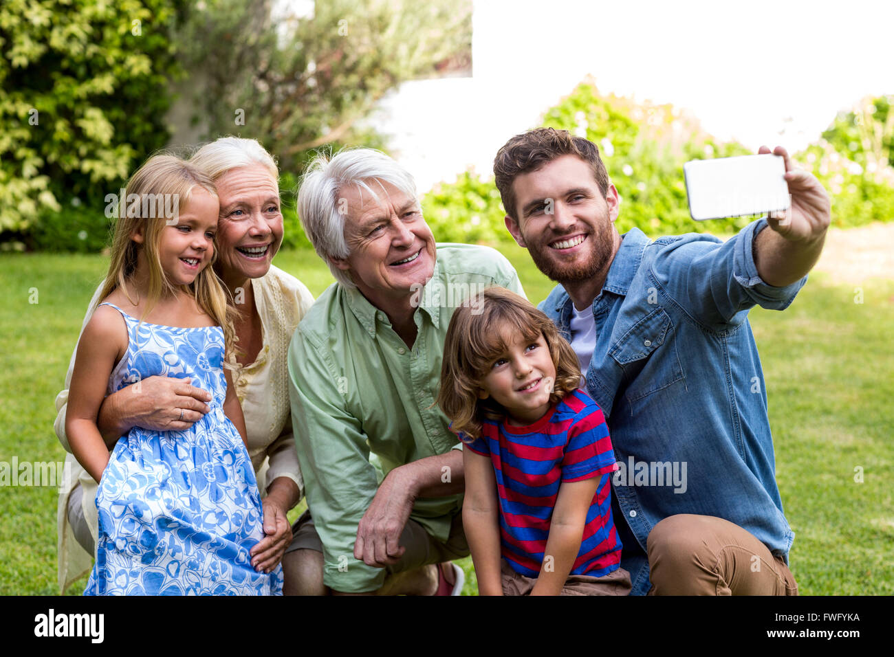 Happy father taking selfie with family in yard - Stock Image