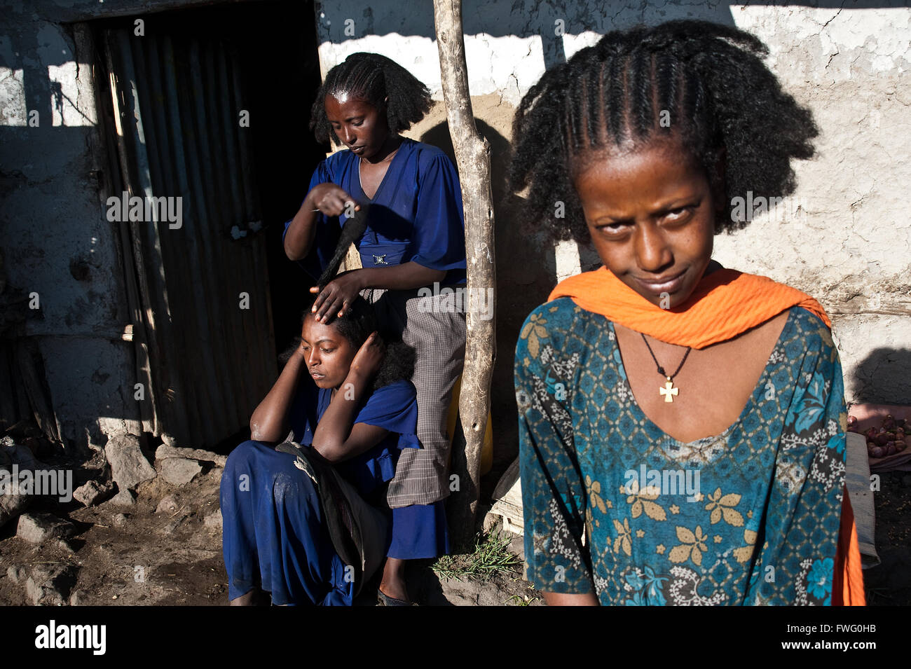 A young woman is combing her sister. In the foreground, a teenage girl with traditional haircut is watching the - Stock Image