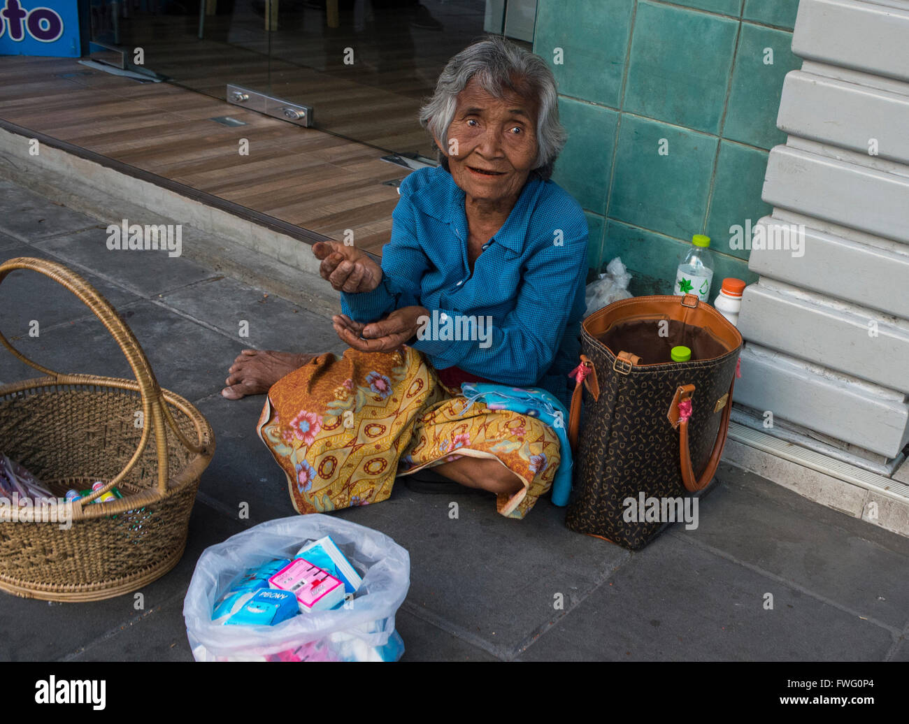 An elderly woman lives by selling small items and begging on the streets of Bangkok, Thailand - Stock Image