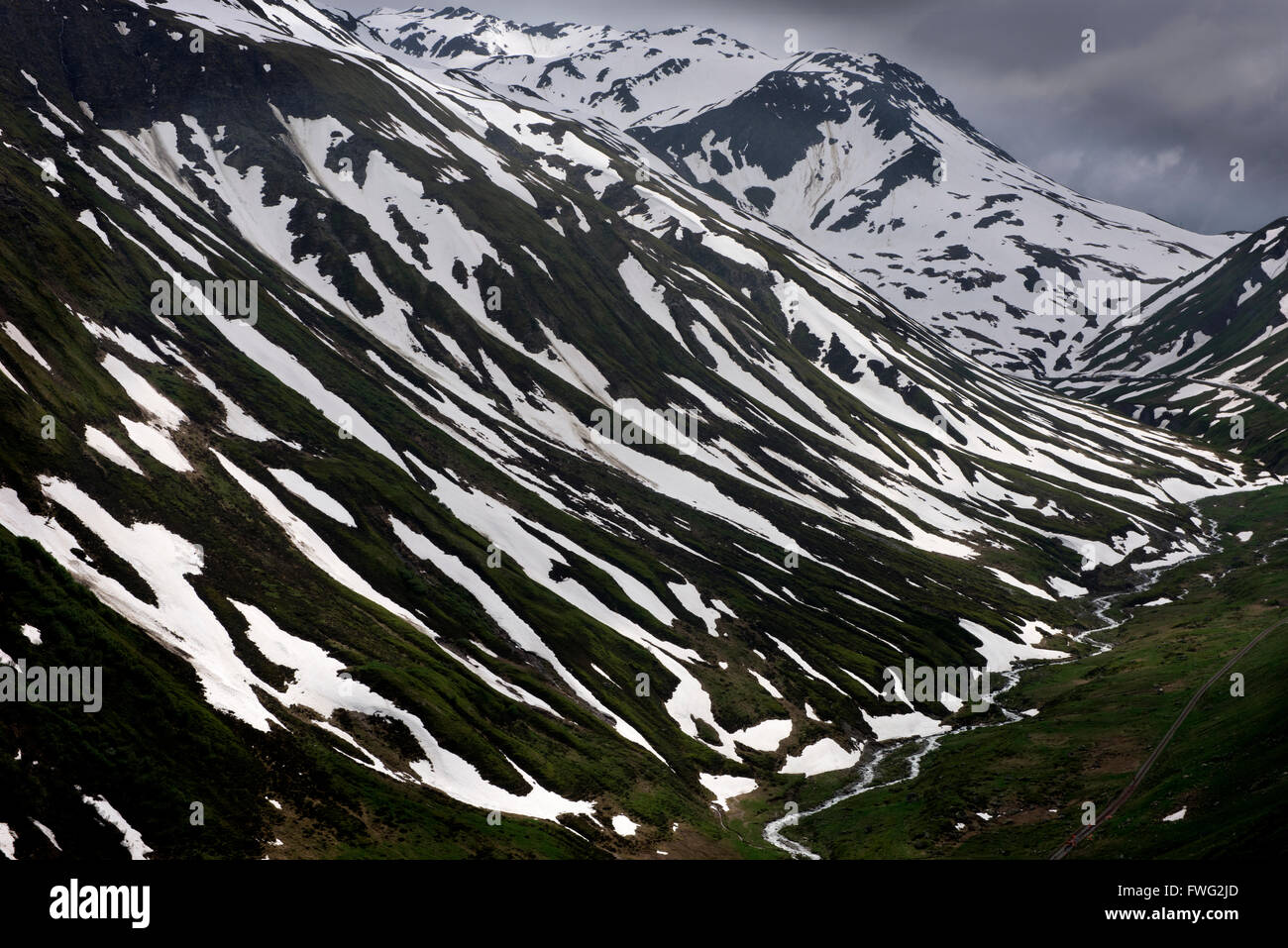 Furka Pass, with an elevation of 2,429 metres (7,969 ft), is a high mountain pass in the Swiss Alps connecting Gletsch, Stock Photo