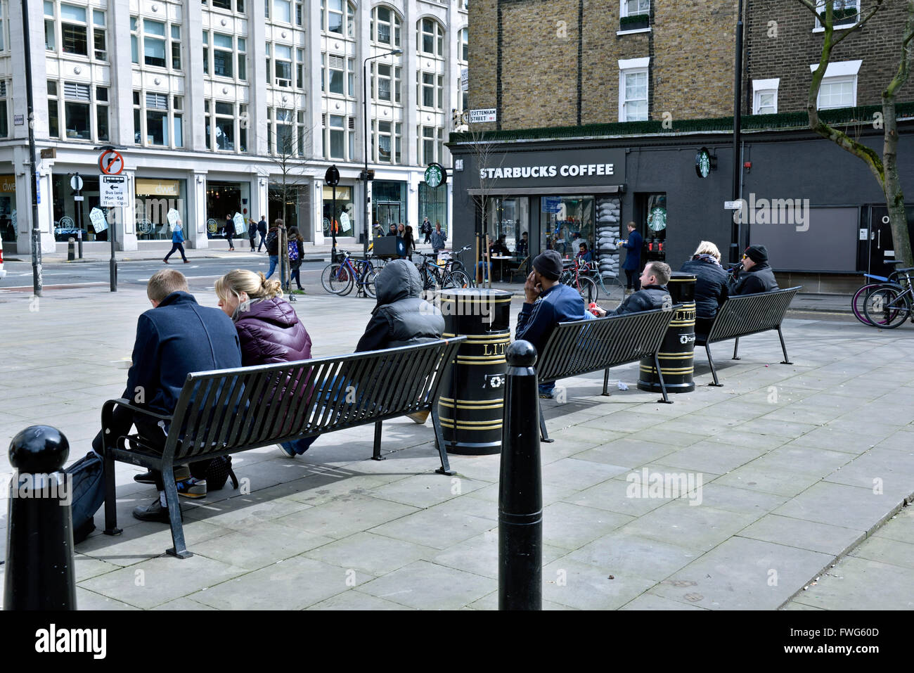 People sitting on benches in public open space off Tottenham Court Road, London Borough of Camden England Britain - Stock Image