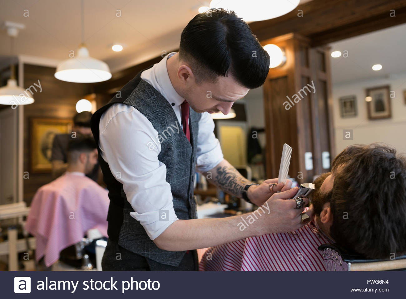 Barber trimming man - Stock Image