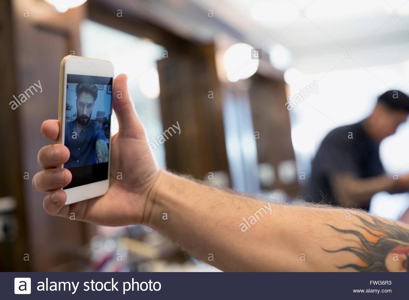 Close up man taking selfie in barber shop - Stock Image