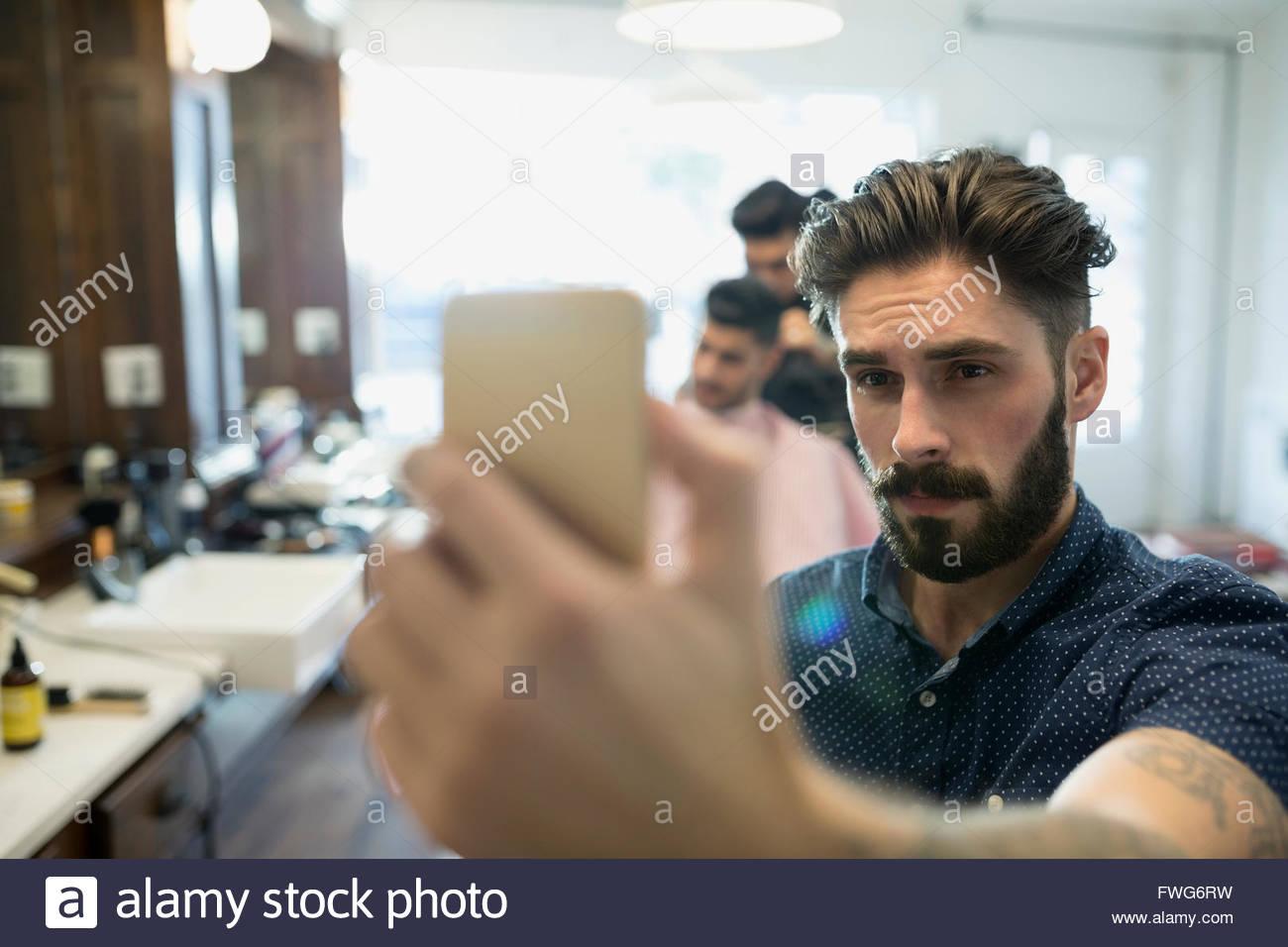 Bearded man taking selfie in barber shop Stock Photo