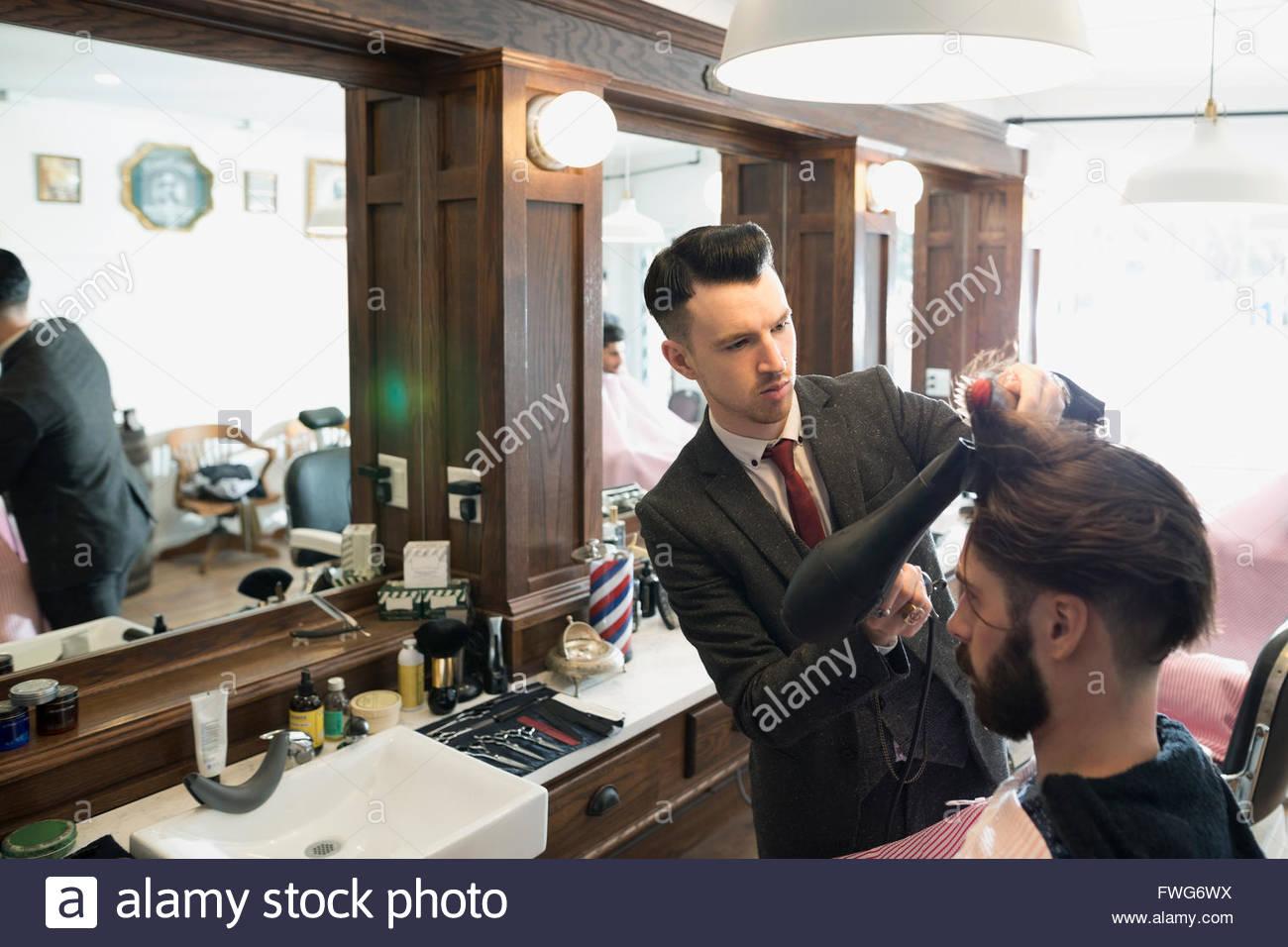 Barber blow drying man - Stock Image