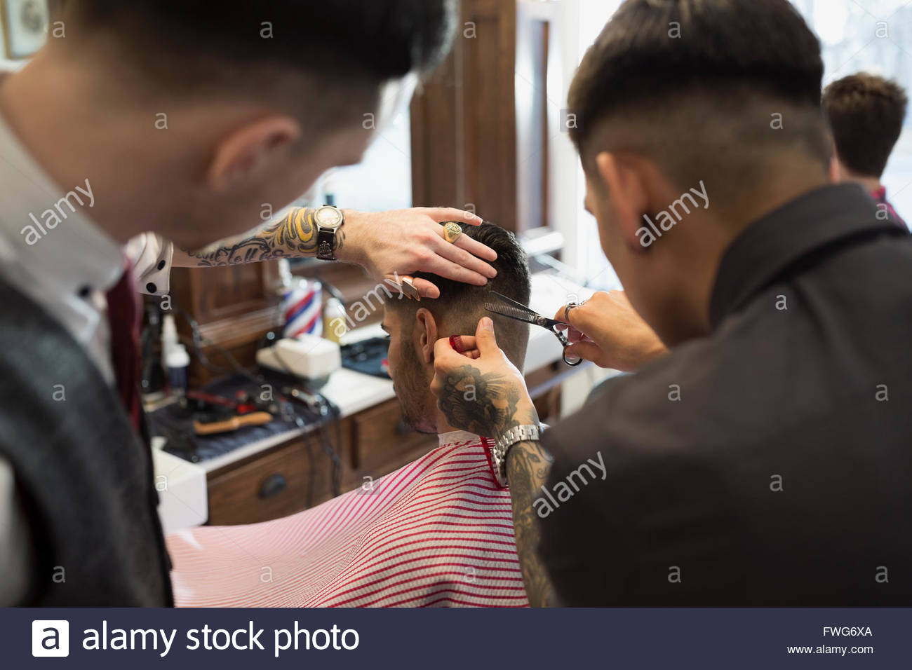 Barbers cutting man - Stock Image