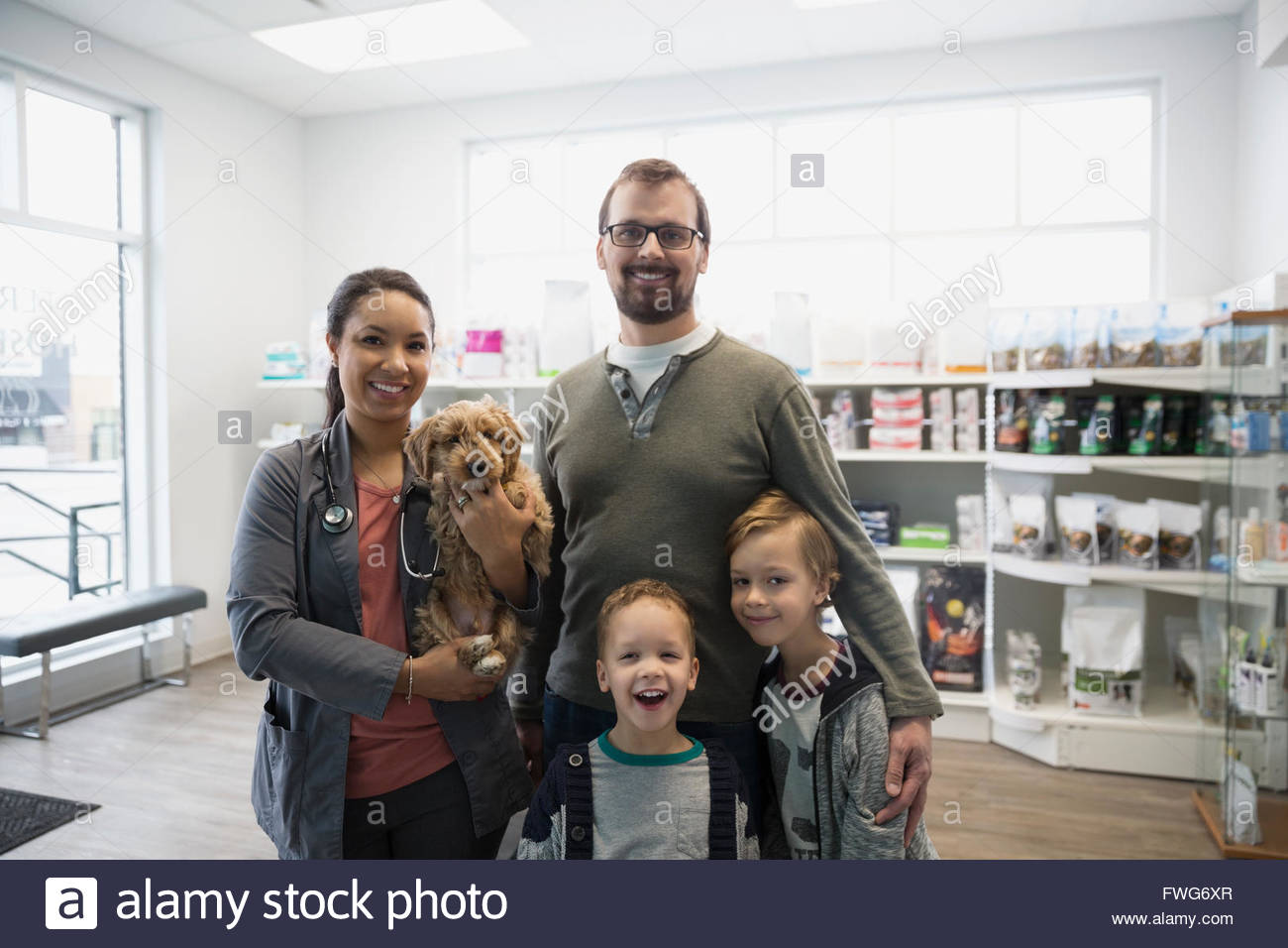 Portrait smiling veterinarian and family with dog clinic - Stock Image