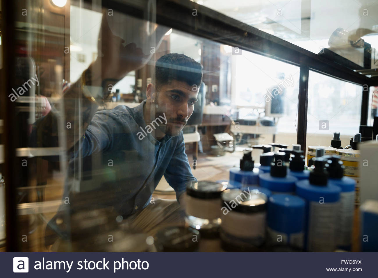 Man browsing hair care products barber shop display - Stock Image