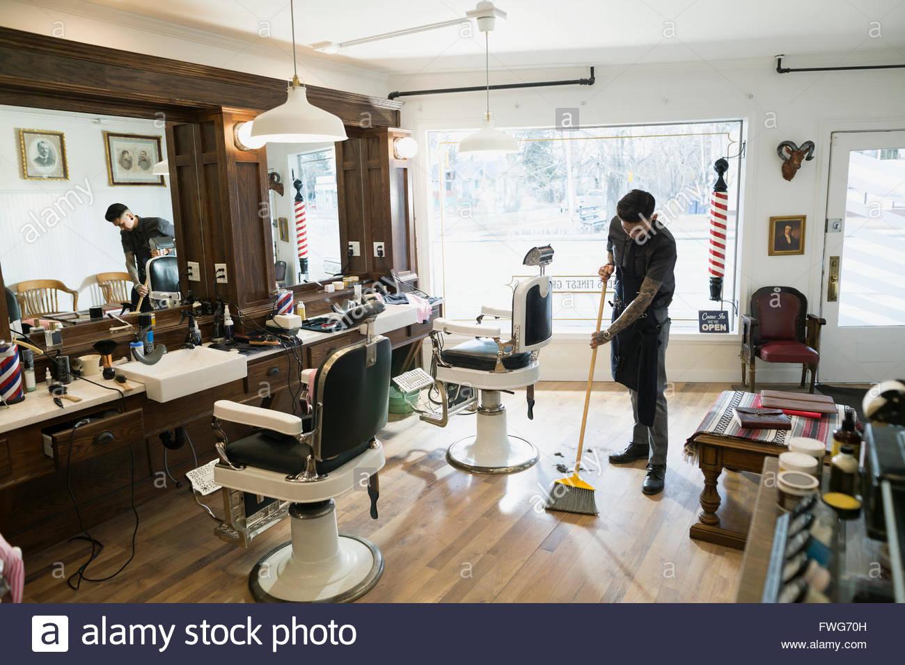 Barber sweeping floor in barber shop - Stock Image