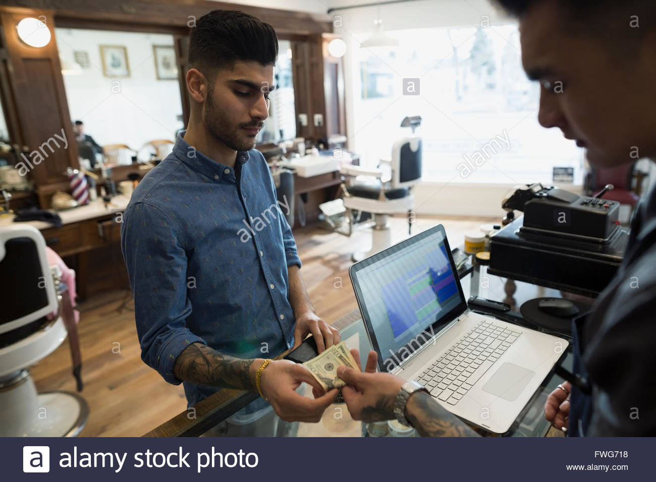 Man paying barber with cash in barber shop - Stock Image