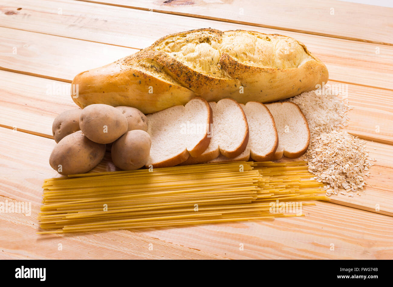 Group of carbohydrates for diet, bread, rice, oat, potatoes, pasta on wood table - Stock Image