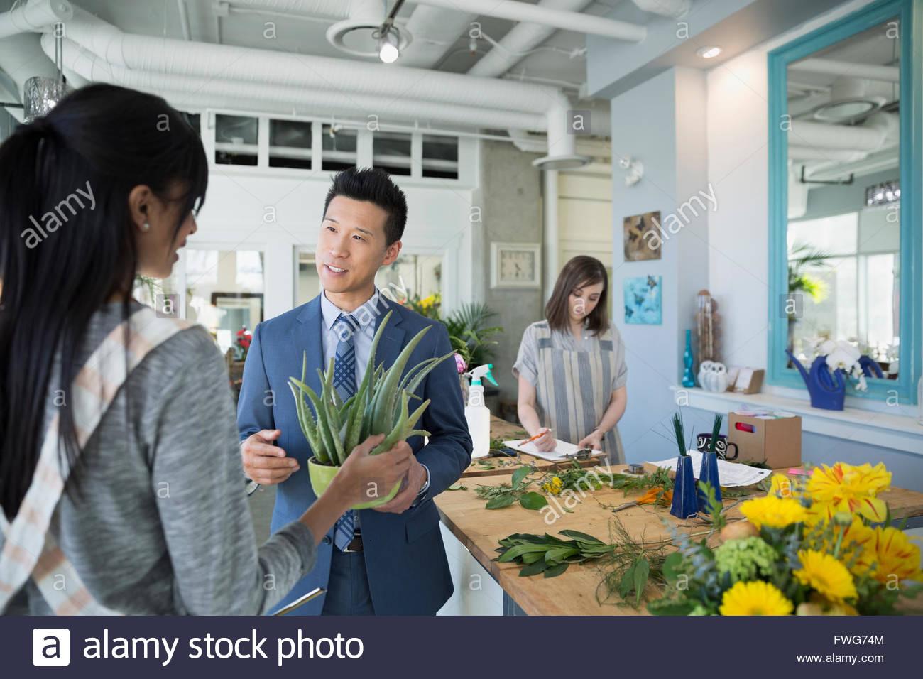 Florist helping customer in flower shop - Stock Image