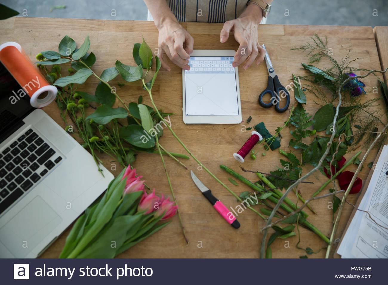 Overhead view florist using digital tablet - Stock Image