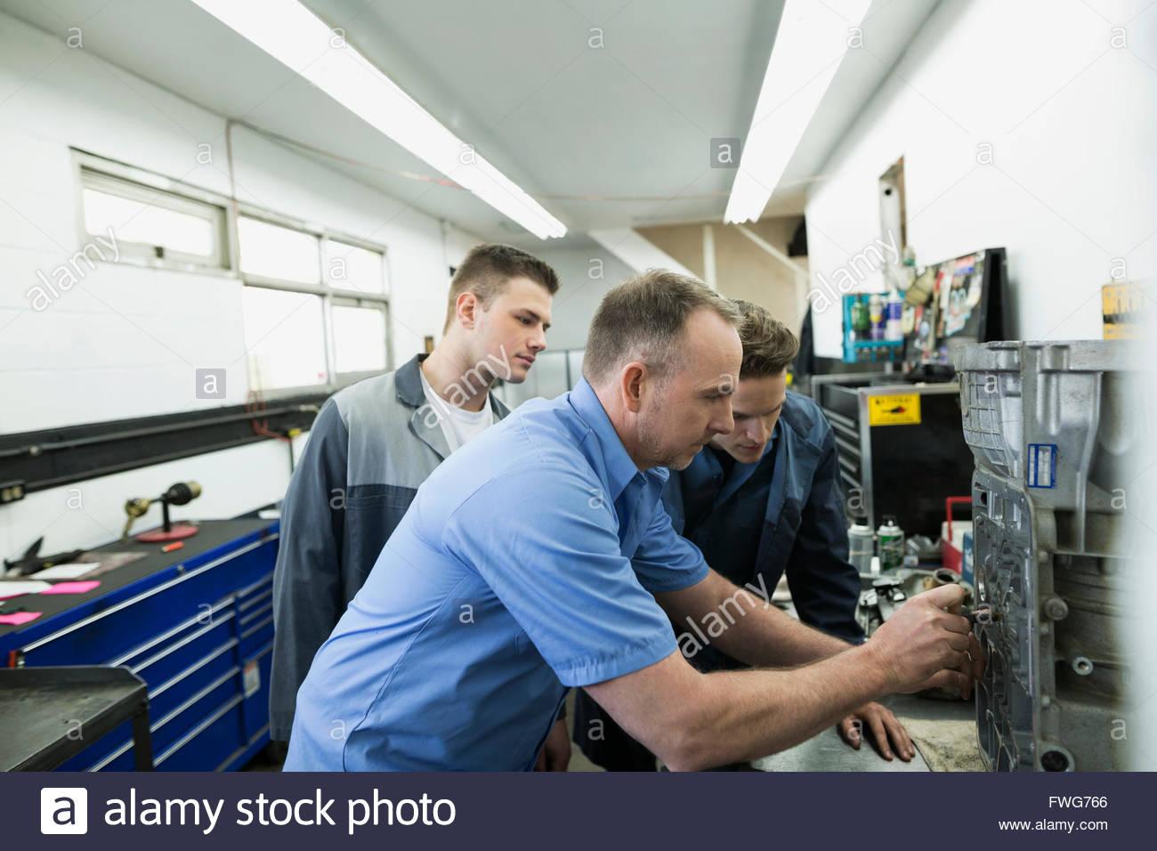 Mechanics examining part in auto repair shop - Stock Image
