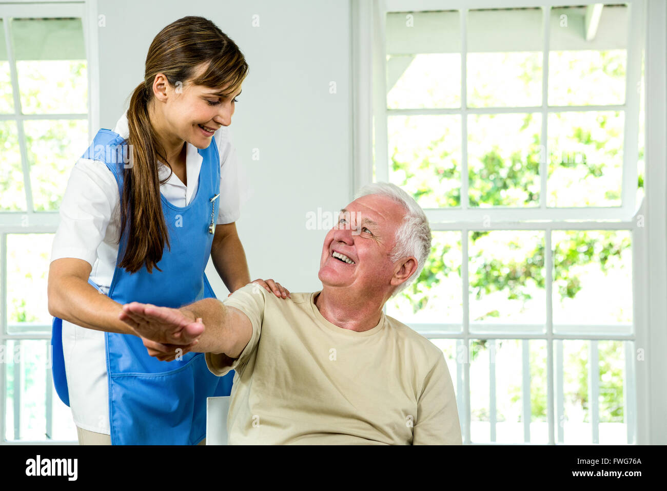 Smiling nurse assisting aged man - Stock Image