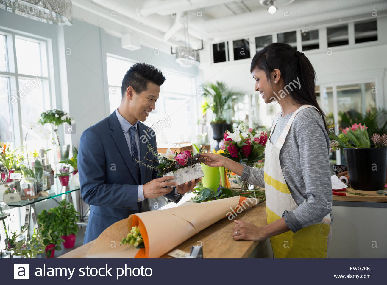 Florist presenting bouquet to man in flower shop - Stock Image