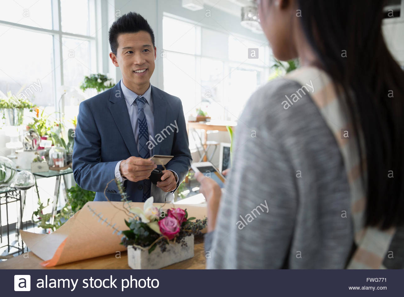 Man paying florist for bouquet in flower shop - Stock Image