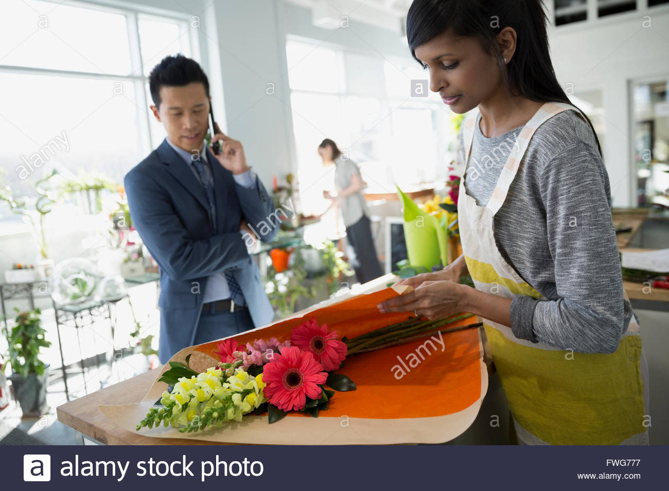 Florist wrapping flowers for man in flower shop - Stock Image
