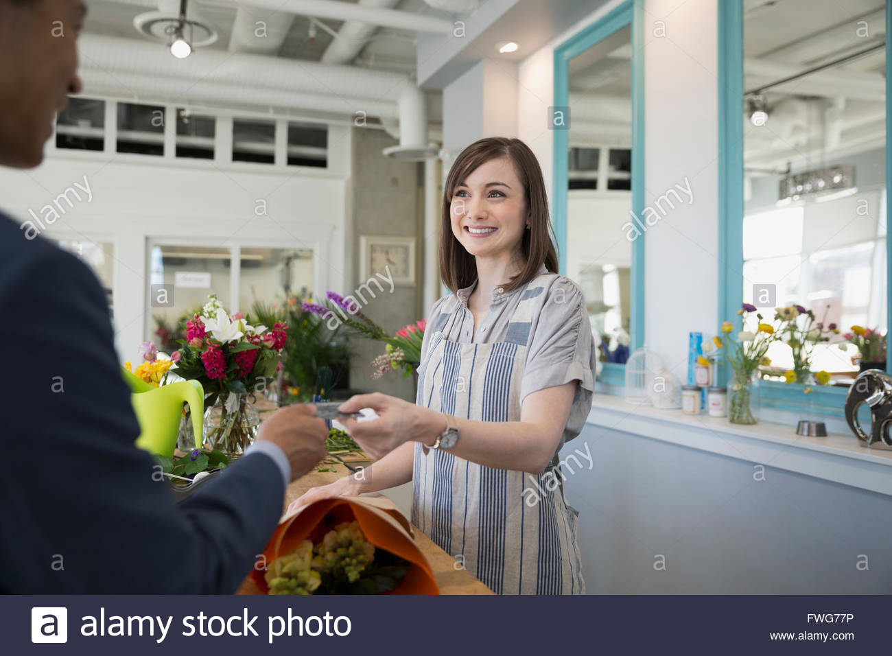 Man paying florist with credit card flower shop - Stock Image