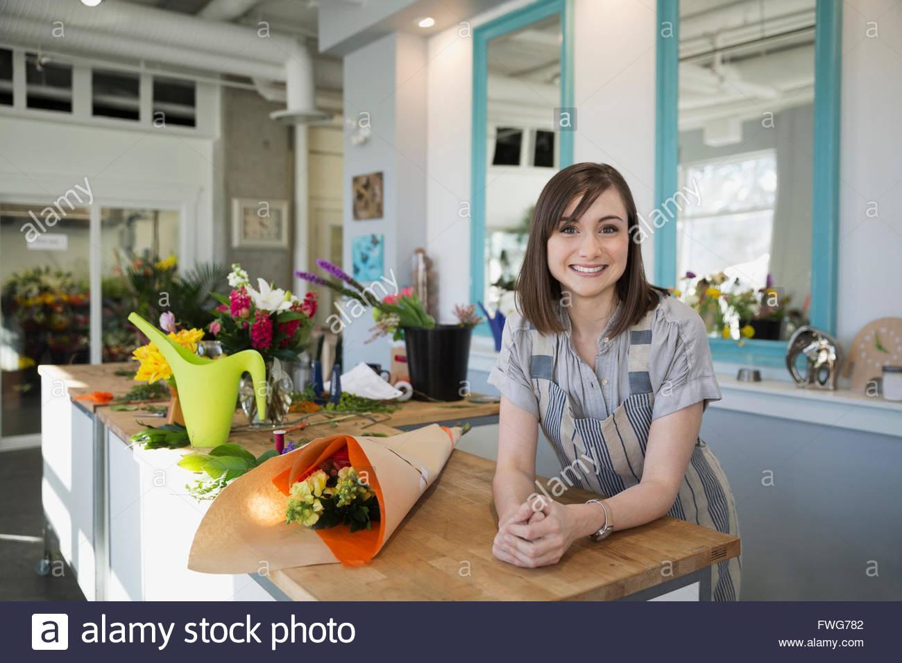 Portrait confident florist in flower shop - Stock Image