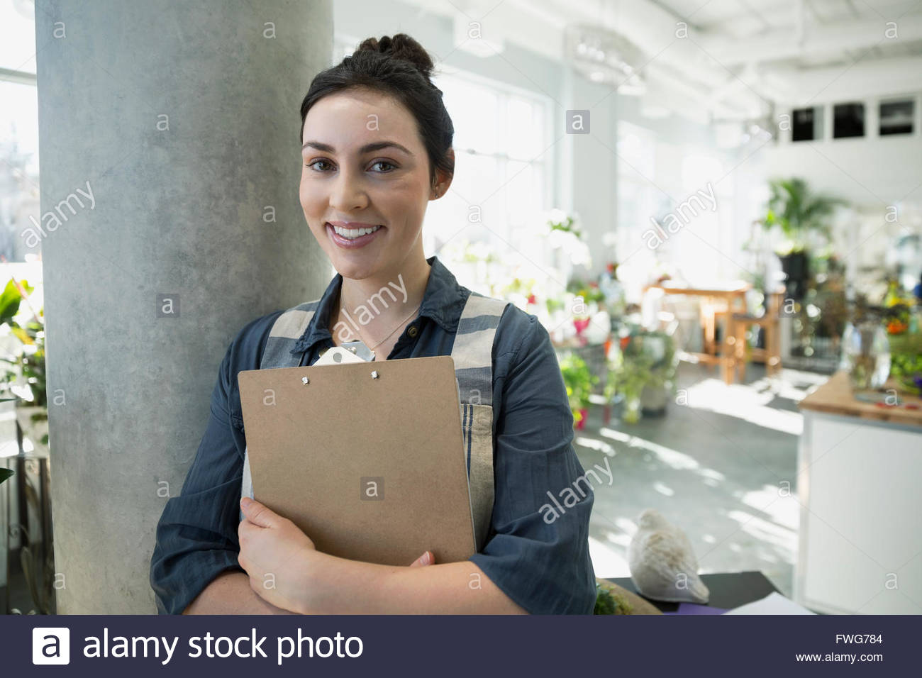 Portrait smiling florist with clipboard in flower shop - Stock Image