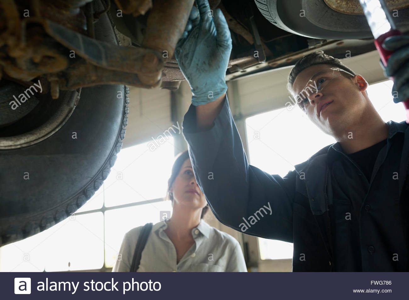 Mechanic and customer under car auto repair shop - Stock Image