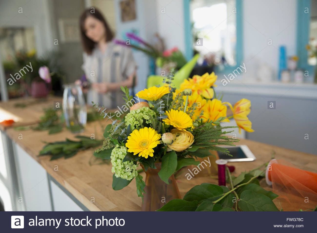 Yellow bouquet on counter in florist shop Stock Photo