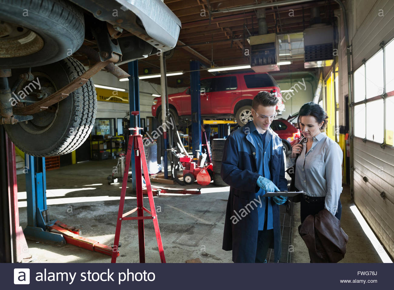 Mechanic with clipboard explaining customer auto repair shop - Stock Image
