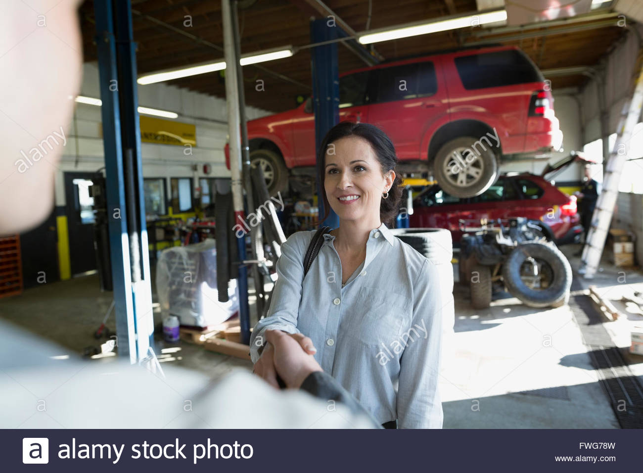 Customer and mechanic shaking hands auto repair shop - Stock Image
