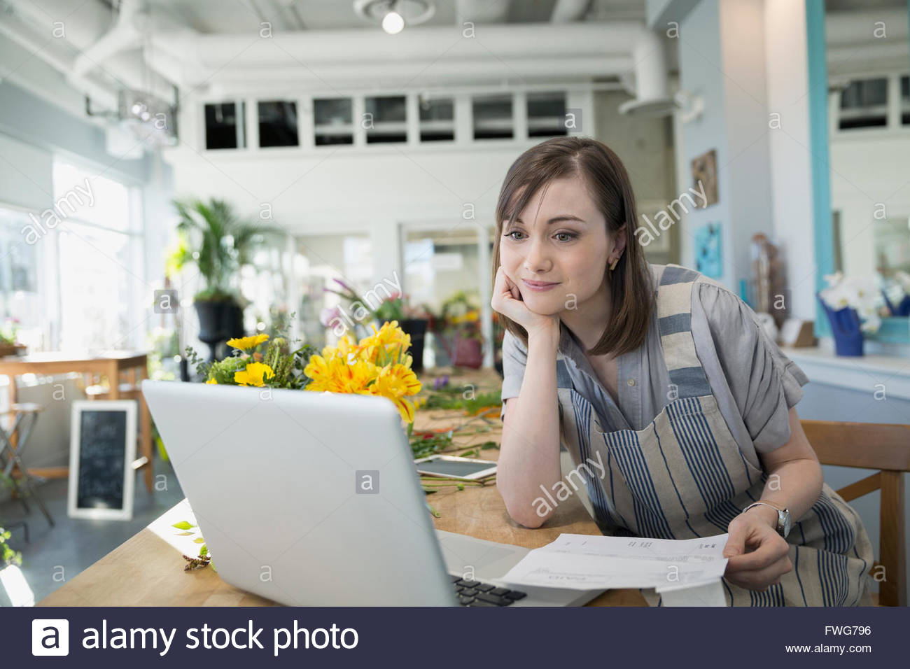 Florists using laptop in flower shop - Stock Image