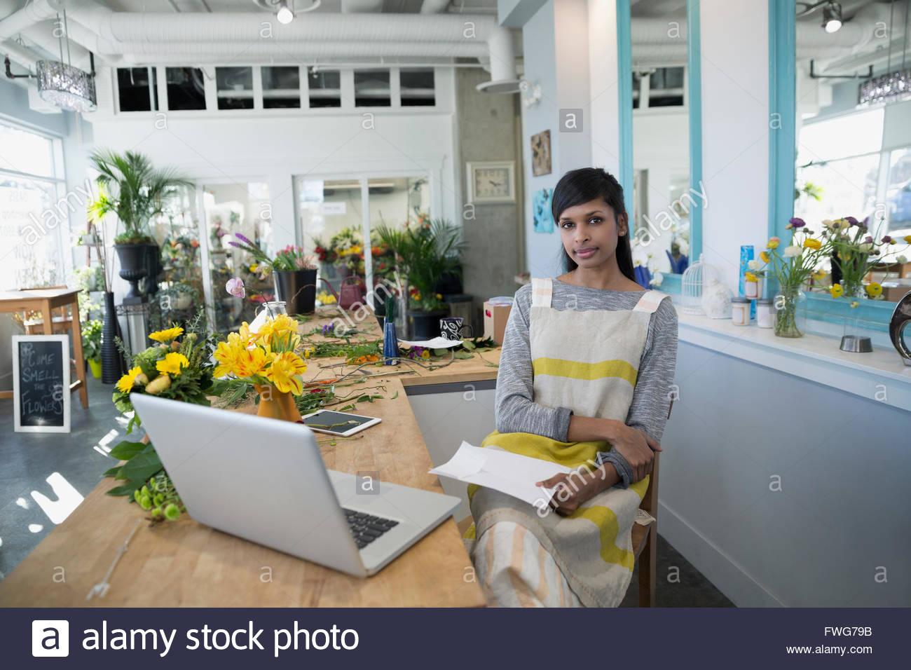 Portrait confident florist at laptop in flower shop - Stock Image