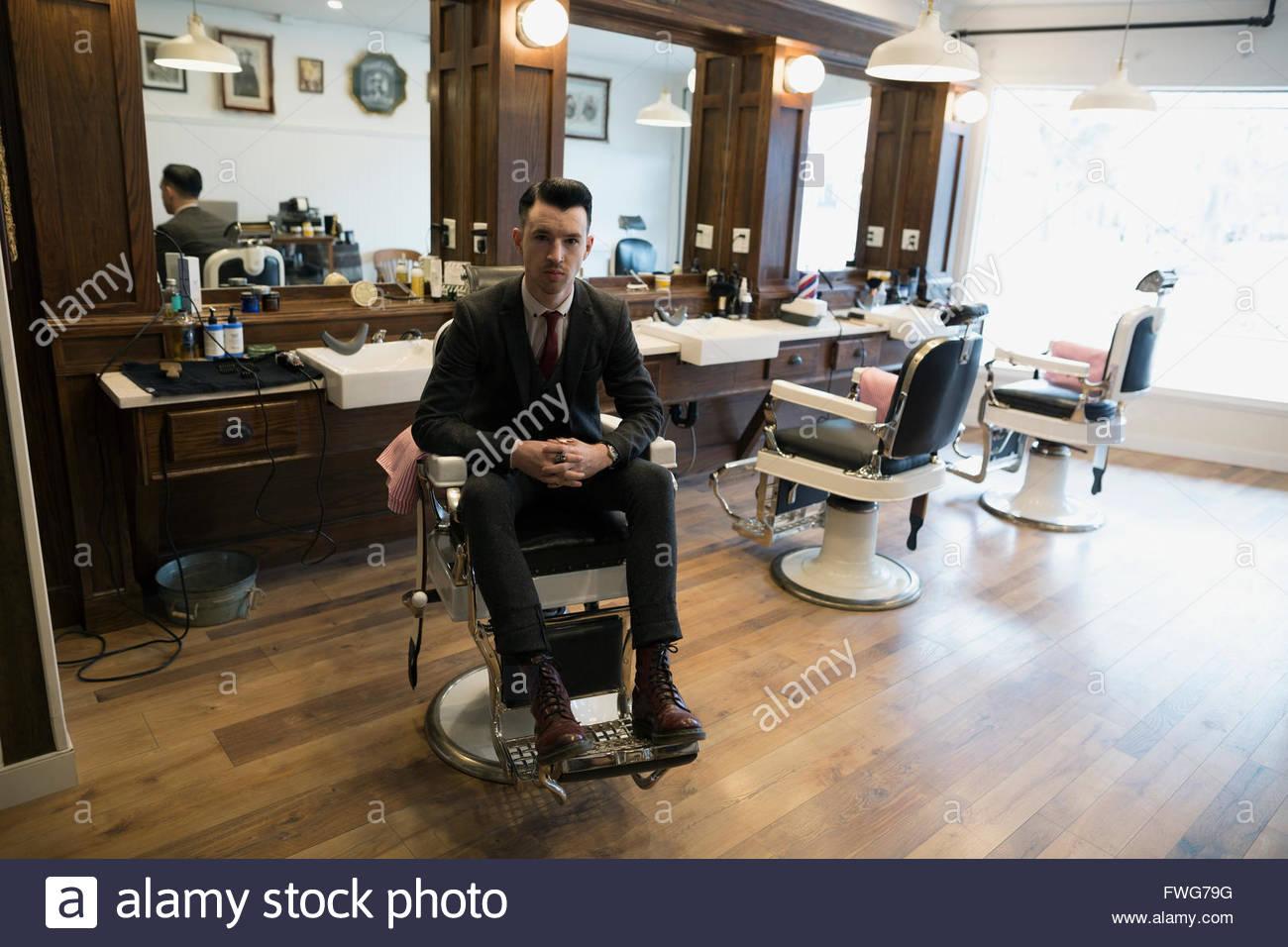 Portrait confident barber wearing suit barber shop chair - Stock Image
